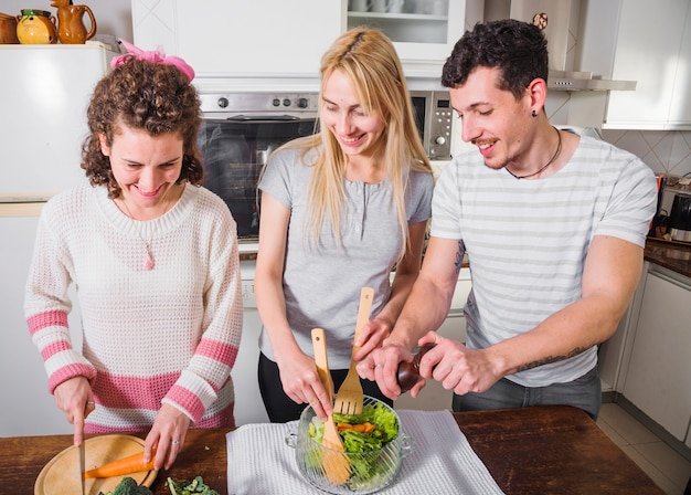 Amigos do sexo feminino felizes preparando a salada na cozinha Foto gratuita