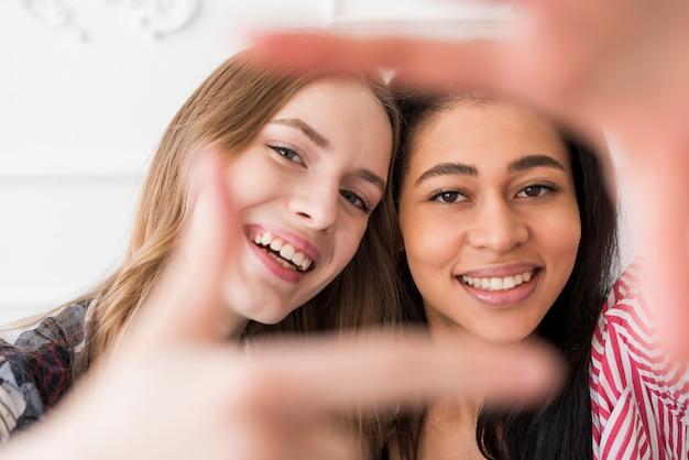 Amigos do sexo feminino gesticulando selfie na câmera Foto gratuita