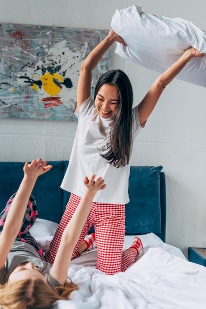Amigos do sexo feminino lutando por travesseiros Foto gratuita