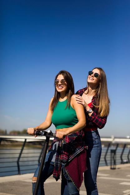 Amigos do sexo feminino muito jovens, montando uma scooter elétrica na rua Foto Premium