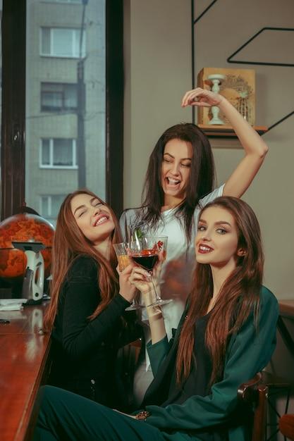 Amigos do sexo feminino tomando uma bebida no bar. eles estão sentados em uma mesa de madeira com coquetéis. eles estão vestindo roupas casuais. Foto gratuita