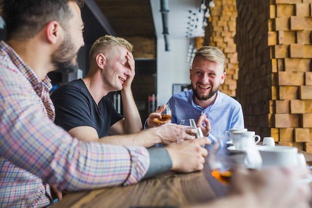 Amigos do sexo masculino a desfrutar da noite bebe no restaurante Foto gratuita