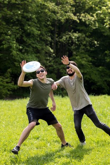 Amigos do sexo masculino a gostar de jogo de frisbee no parque Foto gratuita