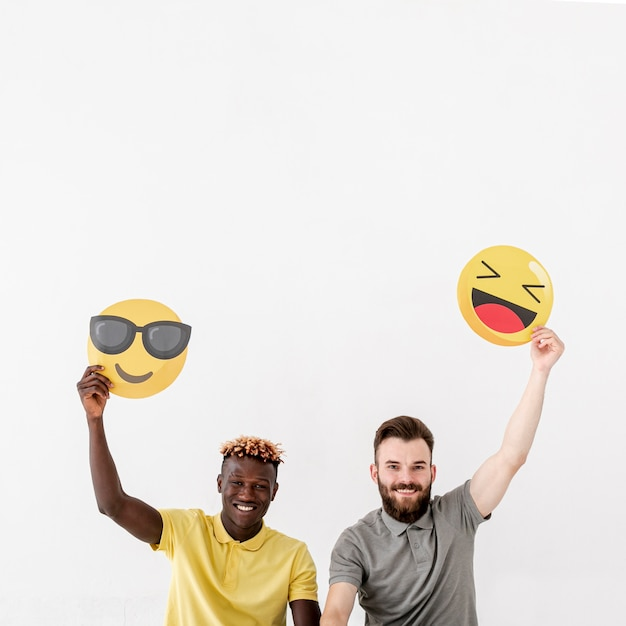 Amigos do sexo masculino cópia-espaço segurando emoji Foto gratuita