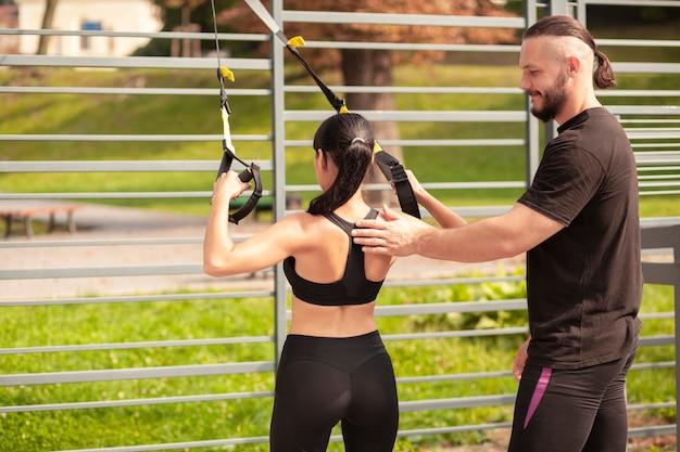 Amigos do sexo masculino ensinando mulher a exercitar corretamente Foto gratuita