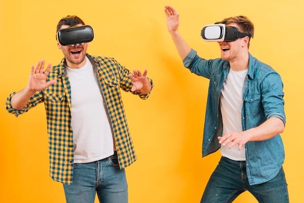Amigos do sexo masculino jovens felizes usando óculos de realidade virtual, tirando sarro, contra um fundo amarelo Foto gratuita