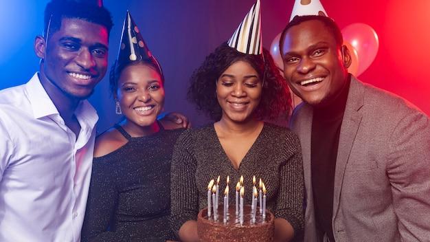 Amigos e bolo de feliz aniversario Foto gratuita