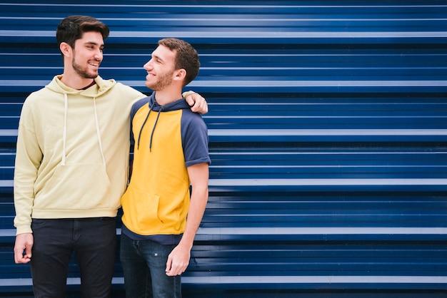 Amigos em camisolas de pé e abraçando Foto gratuita
