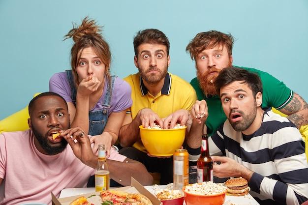 Amigos emocionais amedrontados da geração y passam o tempo juntos, assistem a filmes emocionantes online, comem pizza saborosa, bebem cerveja, têm olhar interessado, isolados contra uma parede azul, aproveitam a televisão. Foto gratuita