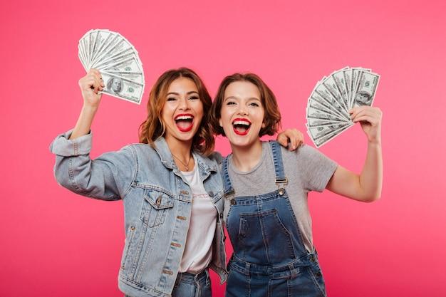 Amigos emocionais de duas mulheres bonitas segurando dinheiro Foto gratuita