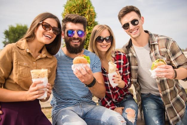 Amigos estão sentados no parque e comem fast food. Foto Premium