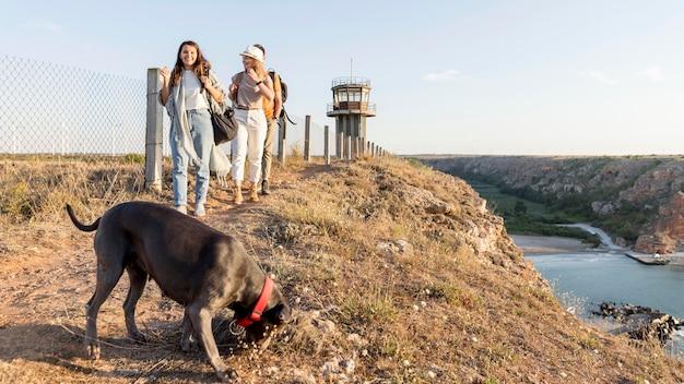 Amigos explorando com seu cachorro Foto gratuita