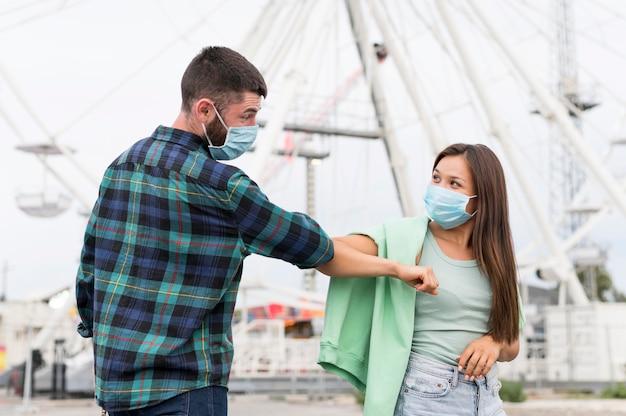 Amigos fazendo saudação de cotovelo enquanto usavam máscaras médicas Foto gratuita