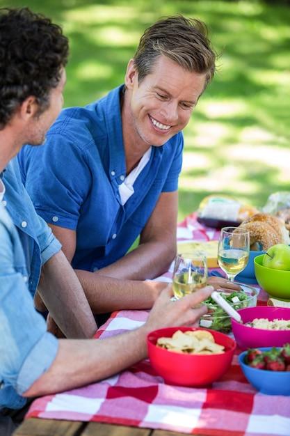 Amigos fazendo um piquenique com vinho Foto Premium