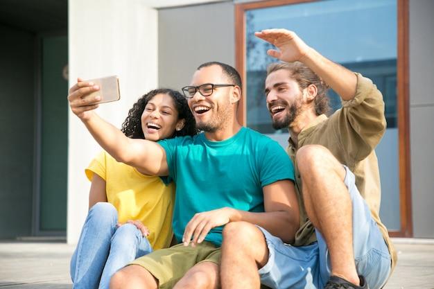 Amigos felizes animados com a conversa com outro amigo Foto gratuita