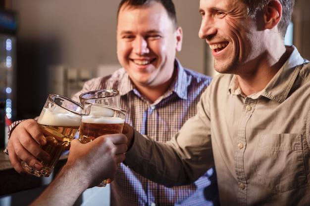 Amigos felizes bebendo cerveja no balcão no pub Foto gratuita