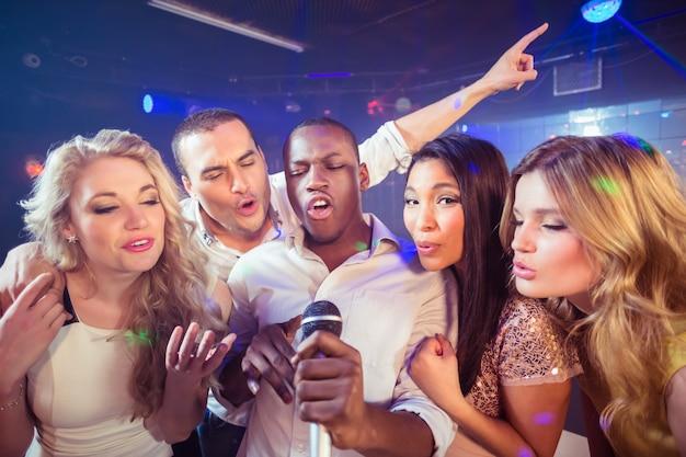 Amigos felizes cantando no karaokê Foto Premium