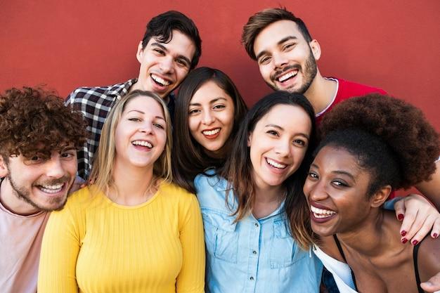 Amigos felizes de diferentes raças e culturas rindo na frente da câmera do telefone - jovens milenares se divertindo juntos - conceito de geração multirracial - foco principal no rosto de menina loira Foto Premium