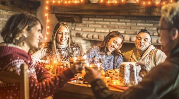 Amigos felizes, degustação de comida doce de natal em casa divertida festa Foto Premium