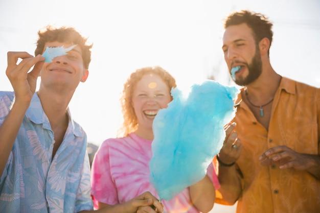 Amigos felizes desfrutando juntos algodão doce Foto gratuita