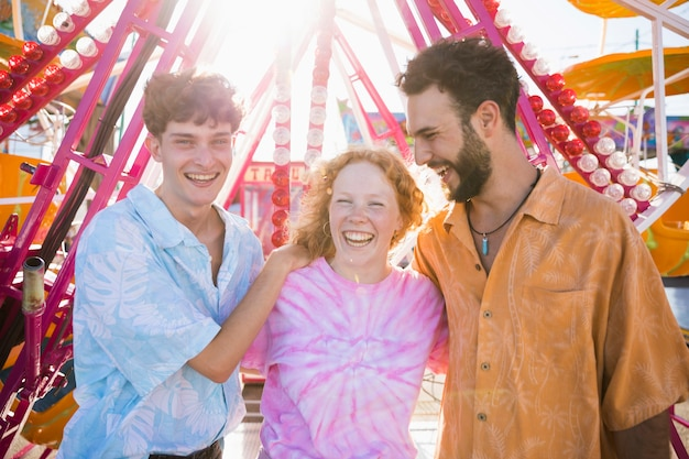 Amigos felizes no parque de diversões, abraçando-se Foto gratuita