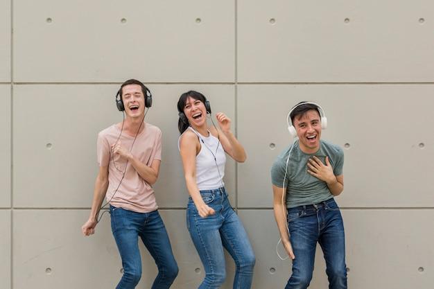 Amigos felizes ouvindo música Foto gratuita