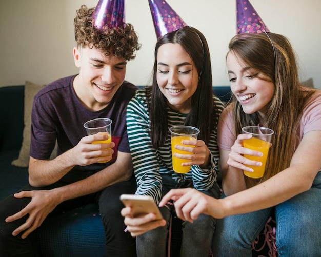 Amigos felizes segurando copos de suco Foto gratuita