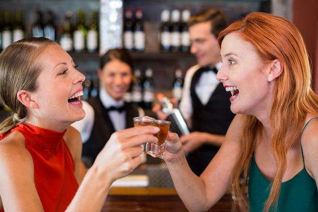 Amigos felizes, segurando um tiro de tequila na frente do balcão de bar Foto Premium