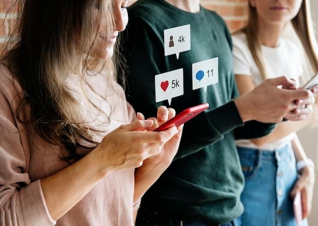 Amigos felizes usando o conceito de mídia social de smartphones Foto Premium