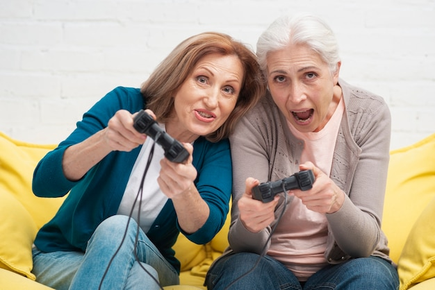 Amigos idosos brincando com controladores Foto gratuita