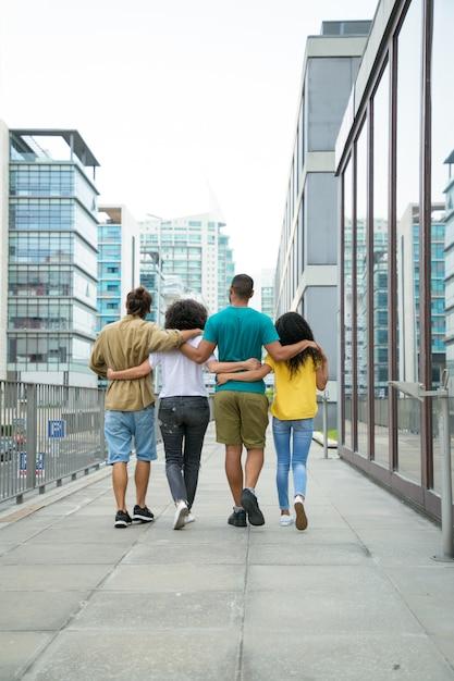 Amigos íntimos andando pela cidade juntos Foto gratuita