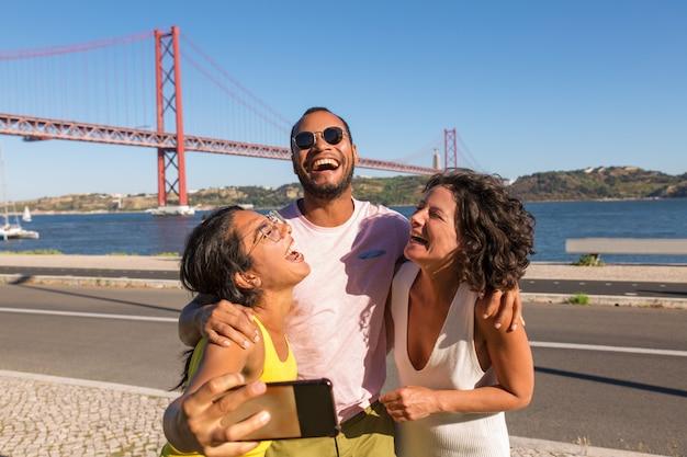 Amigos íntimos felizes curtindo conhecer e tirar uma selfie em grupo Foto gratuita