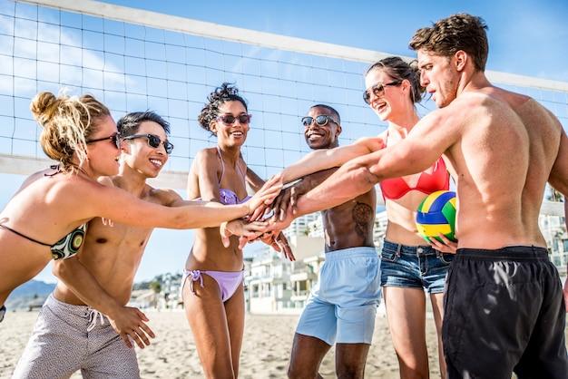 Amigos jogam vôlei de praia Foto Premium