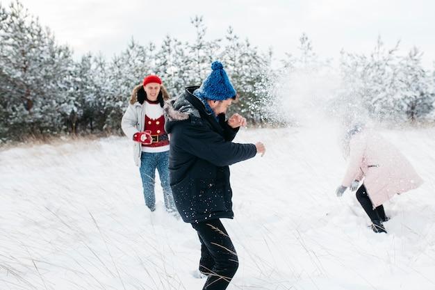 Amigos jogando bolas de neve na floresta de inverno Foto gratuita