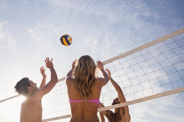 Amigos jogando vôlei de praia Foto Premium