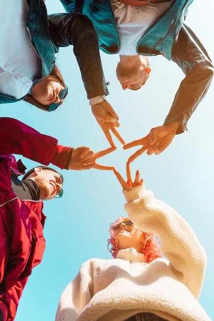 Amigos, juntando as mãos com gesto de paz Foto gratuita