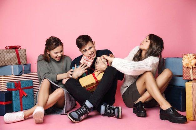 Amigos lutando por caixas de presente de natal em rosa Foto gratuita