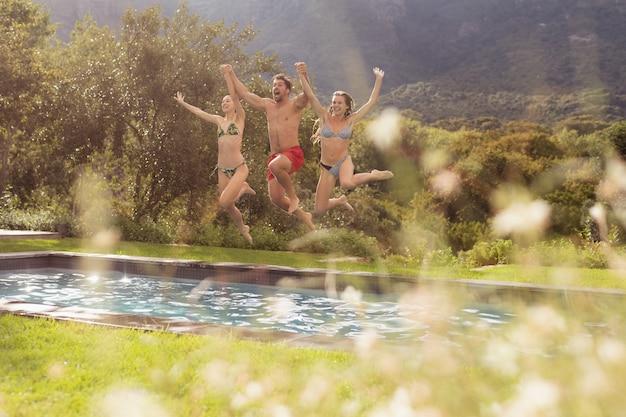 Amigos masculinos e femininos, pulando na piscina no quintal Foto gratuita