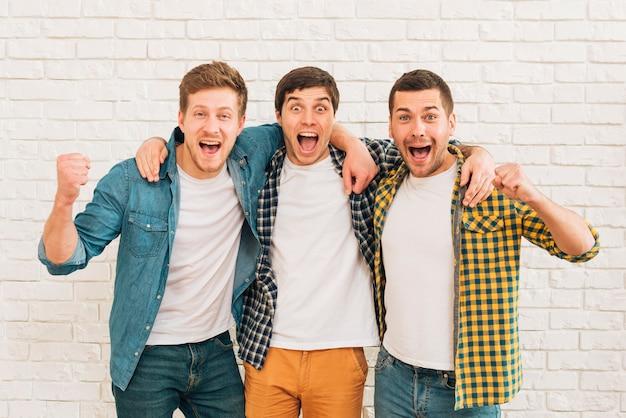Amigos masculinos novos entusiasmado que estão de encontro à parede branca que aperta seu punho Foto gratuita