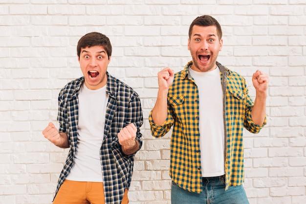 Amigos masculinos novos entusiasmado que estão de encontro à parede de tijolo branca que aperta seu punho Foto gratuita