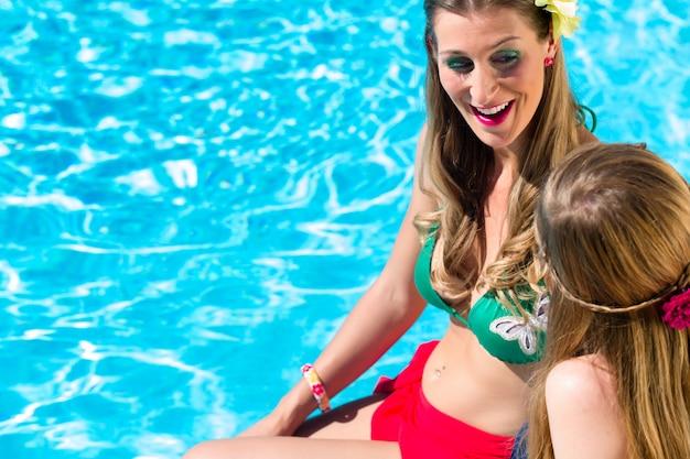 Amigos menina, bronzeando-se, em, piscina, frente, água Foto Premium