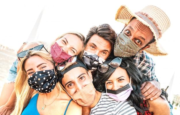 Amigos milenares multirraciais tomando selfie sorrindo por trás de máscaras faciais Foto Premium
