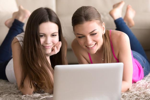 Amigos mulheres, mentindo chão, frente, laptop Foto gratuita