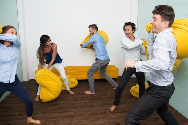 Amigos multiétnicas de êxtase que lutam travesseiros Foto gratuita