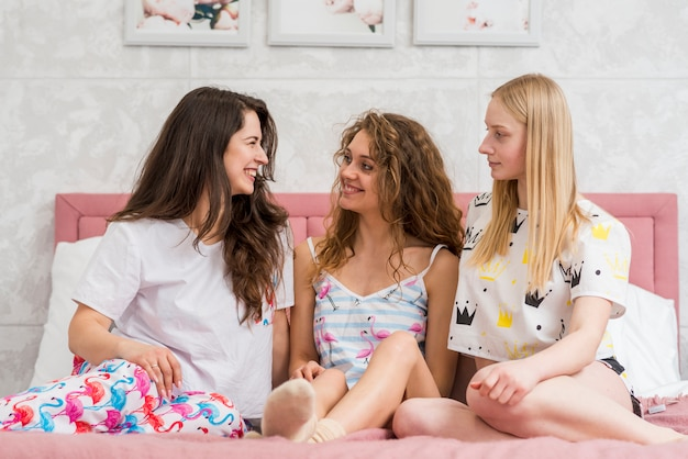 Amigos na festa de pijama posando para uma foto Foto gratuita