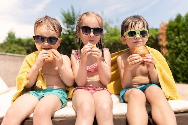 Amigos na piscina comendo Foto gratuita