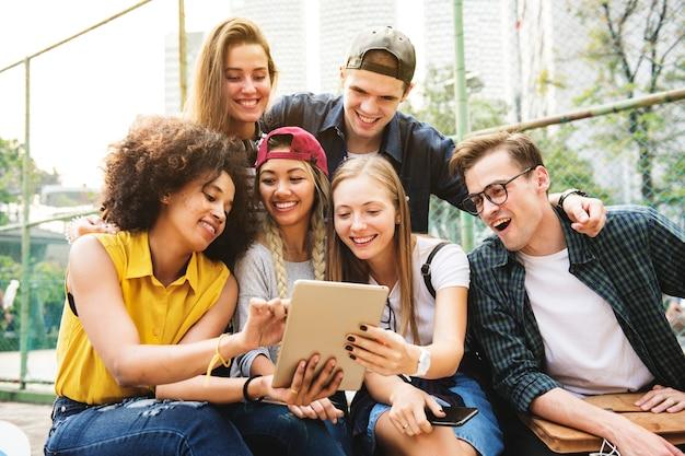 Amigos no parque usando um tablet digital milenar e conceito de cultura de juventude Foto Premium