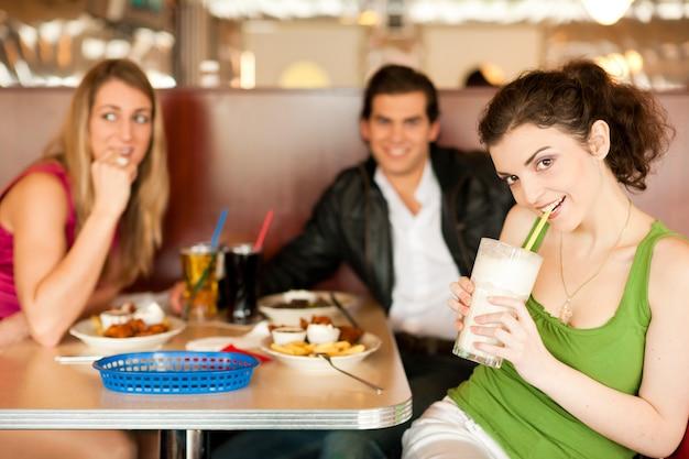 Amigos no restaurante comendo fast-food Foto Premium
