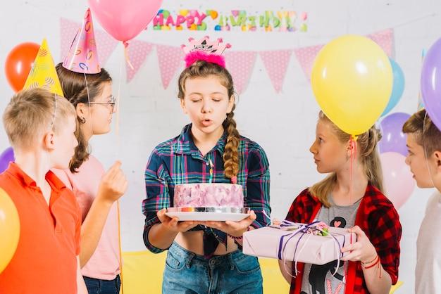 Amigos, olhar, menina, com, bolo aniversário, soprando, vela Foto gratuita
