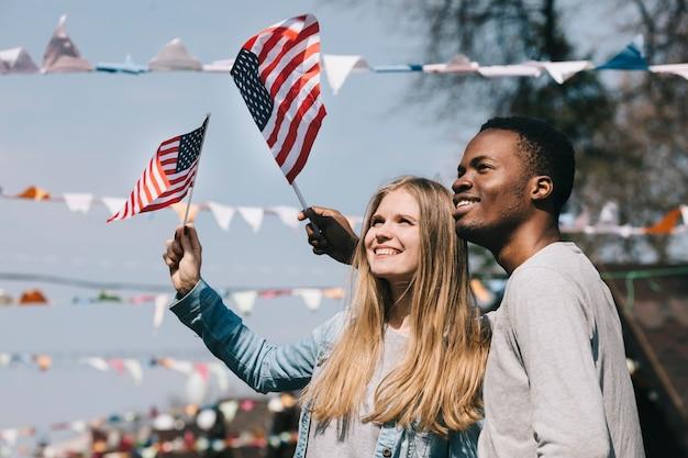 Amigos patrióticos multiétnicas, acenando bandeiras dos eua Foto gratuita